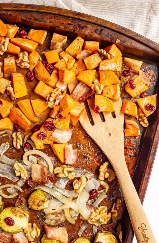 Roasted sweet potatoes on a sheet pan with walnuts and dried cranberries