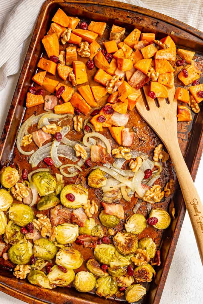 Mixed roasted vegetables on a sheet pan with a wooden spatula