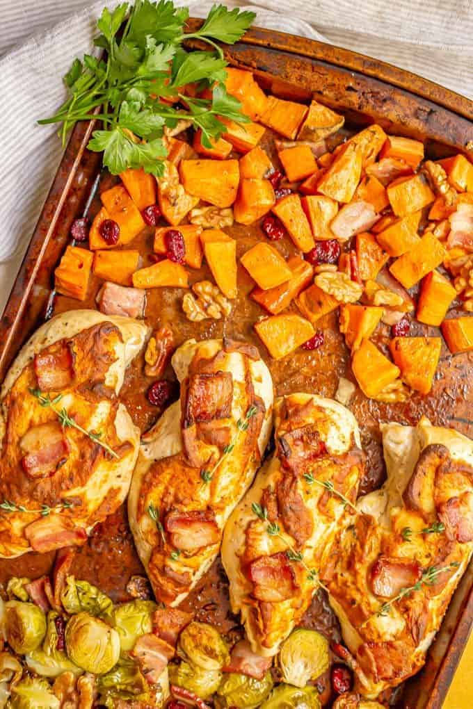 Sheet pan harvest chicken and vegetables is loaded with tender, juicy chicken breasts, sweet potatoes, Brussels sprouts, bacon and more for a warm, delicious, easy dinner! #sheetpan #chickenrecipes #chickendinner #dinnerideas #easyrecipe
