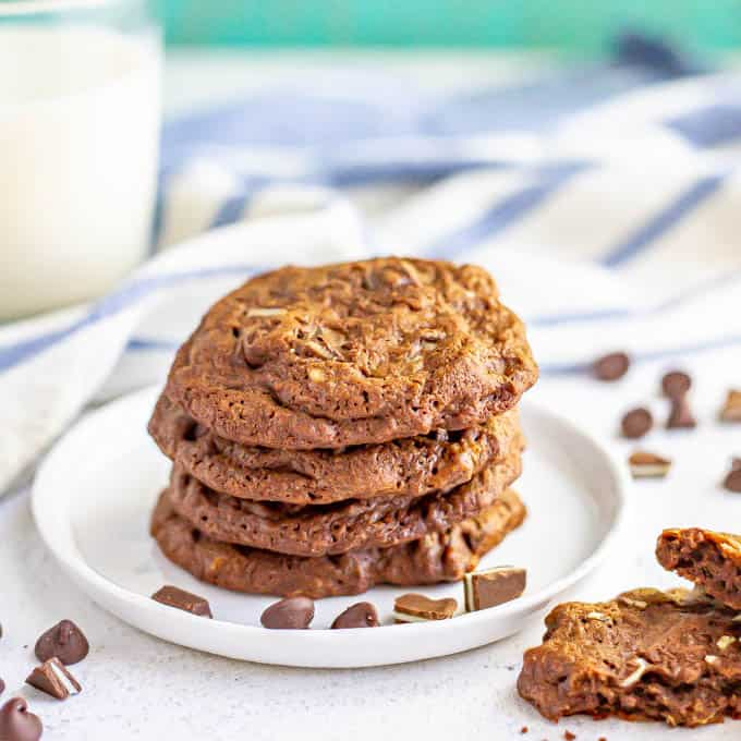 A stack of chocolate cookies on a white plate with a glass of milk