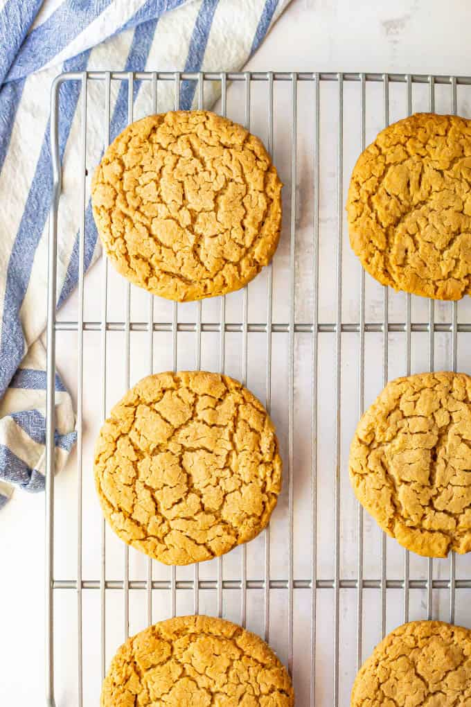 Large peanut butter cookies on a cooling rack with a blue striped towel nearby