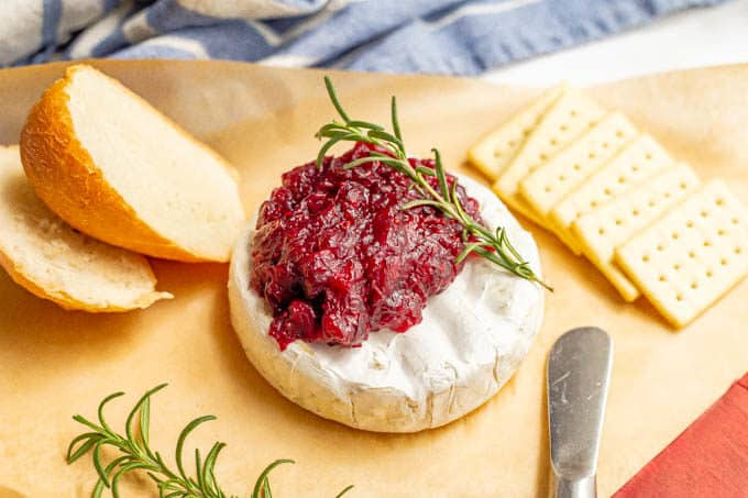 Warm baked brie with cranberry sauce, served with crackers and fresh bread