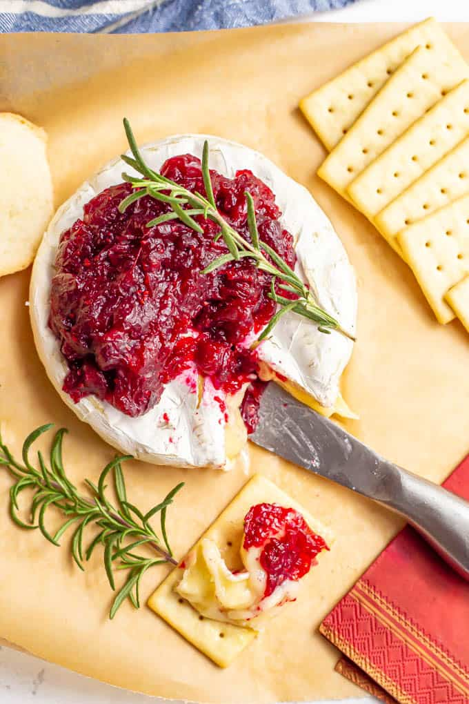 Holiday baked brie with cranberry sauce and rosemary, served with crackers