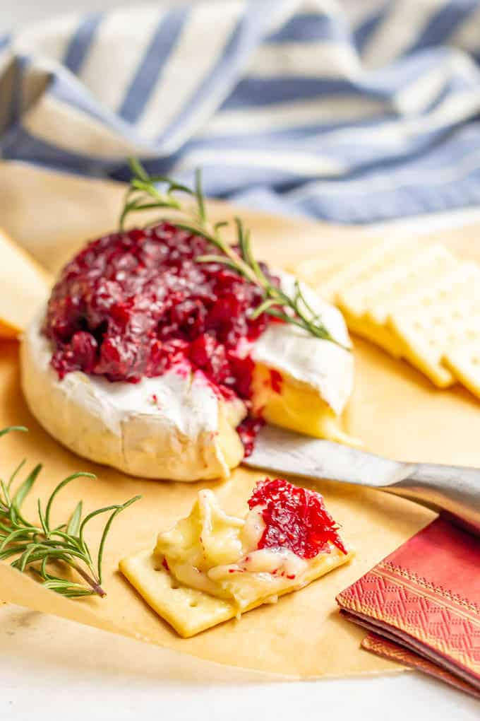 Baked brie with cranberry sauce sliced and served with crackers