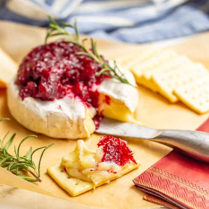 A cracker spread with brie cheese and cranberry sauce
