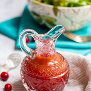 Fresh cranberry vinaigrette dressing in a pouring glass with fresh cranberries nearby