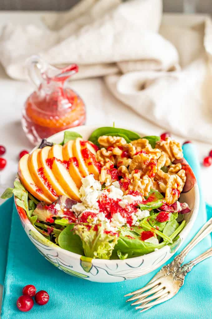 A salad bowl with greens, apples, walnuts and feta cheese and cranberry vinaigrette drizzled over top