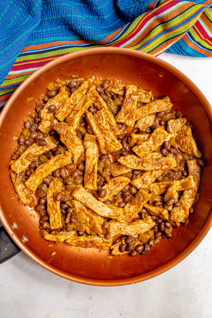 Skillet with cooked pork strips, black beans and green chilies