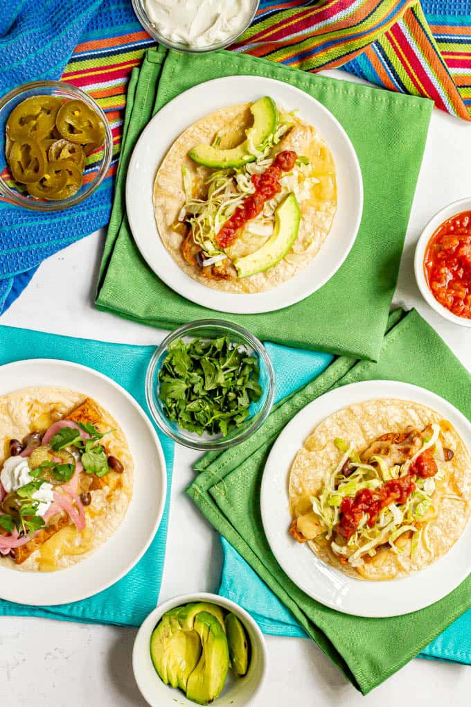 Trio of easy pork tostadas with various toppings arranged on plates with colorful napkins underneath
