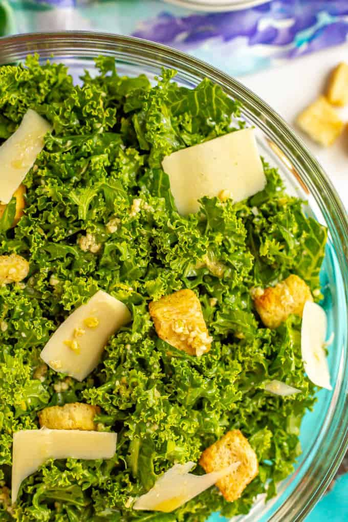 Close up of kale salad in a glass bowl with croutons, Parmesan cheese and Caesar dressing