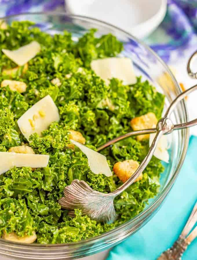 Salad tongs in a glass bowl with kale Caesar salad