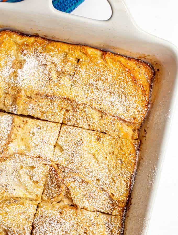 Baked French toast casserole in the white casserole dish with powdered sugar on top