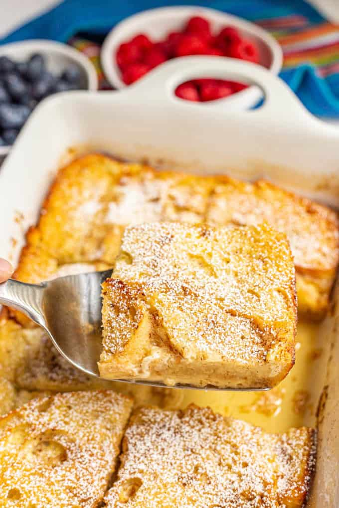 A slice of French toast casserole being lifted out of the baking dish