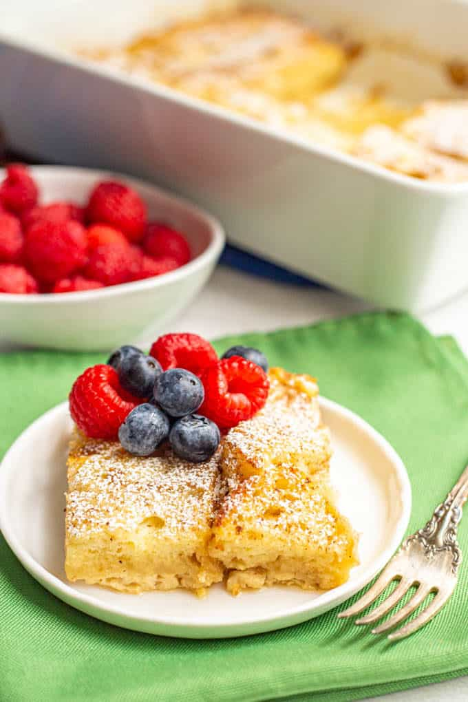 A slice of overnight French toast served on a white plate with fresh berries and a fork alongside