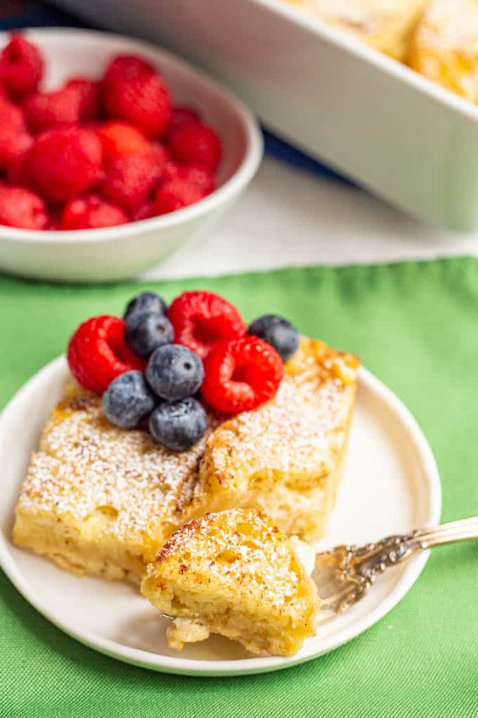 Baked French toast served on a white plate with fresh berries on top and a bite taken out with a fork
