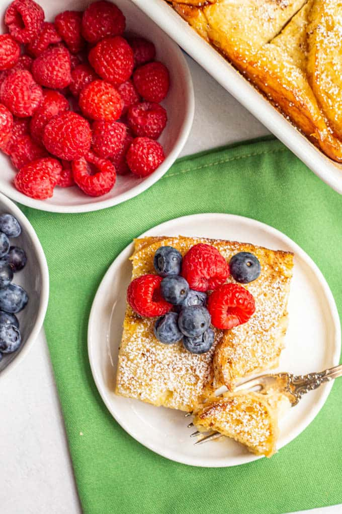 Baked French toast served on a white plate with fresh berries on top