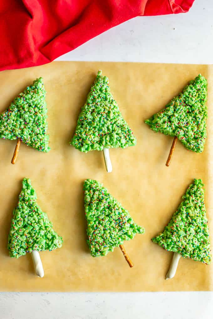 A group of Christmas Rice Krispies treats with sprinkles on top on a piece of parchment paper