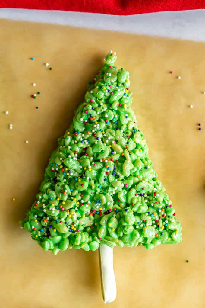 Christmas tree made of Rice Krispies cereal and decorated with sprinkles and a pretzel stem