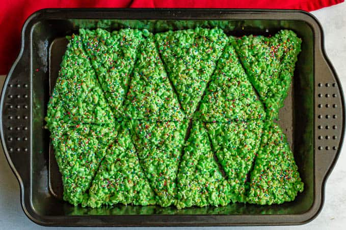 Pan of green crispy rice treats topped with sprinkles and cut into triangles
