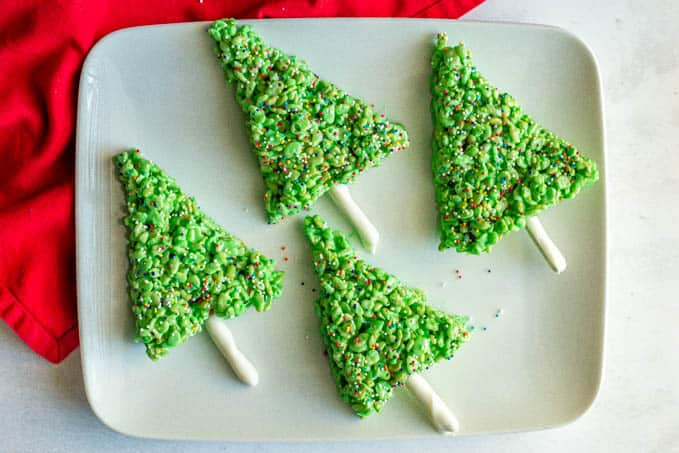 A group of green holiday Rice Krispie trees with sprinkles on a white platter