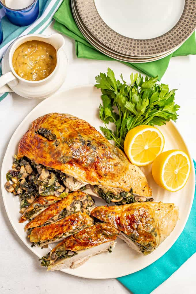A browned roasted turkey breast stuffed with spinach and mushrooms, served on a white platter