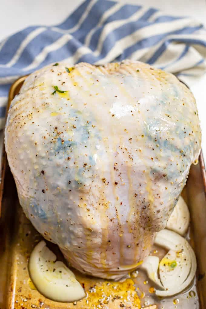 A raw turkey breast that's been stuffed with a spinach and mushroom mixture