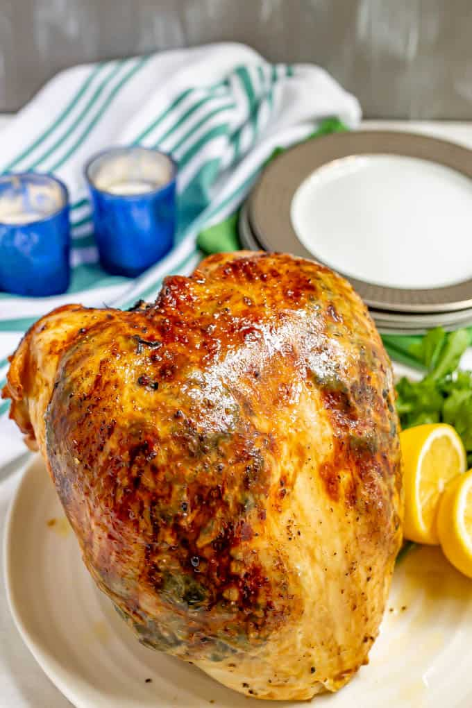 A whole roasted turkey breast on a white platter with lemons and parsley
