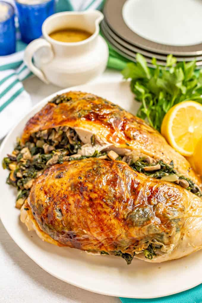 Two roasted, browned turkey breast halves with spinach mushroom stuffing presented on a white platter with parsley and lemon