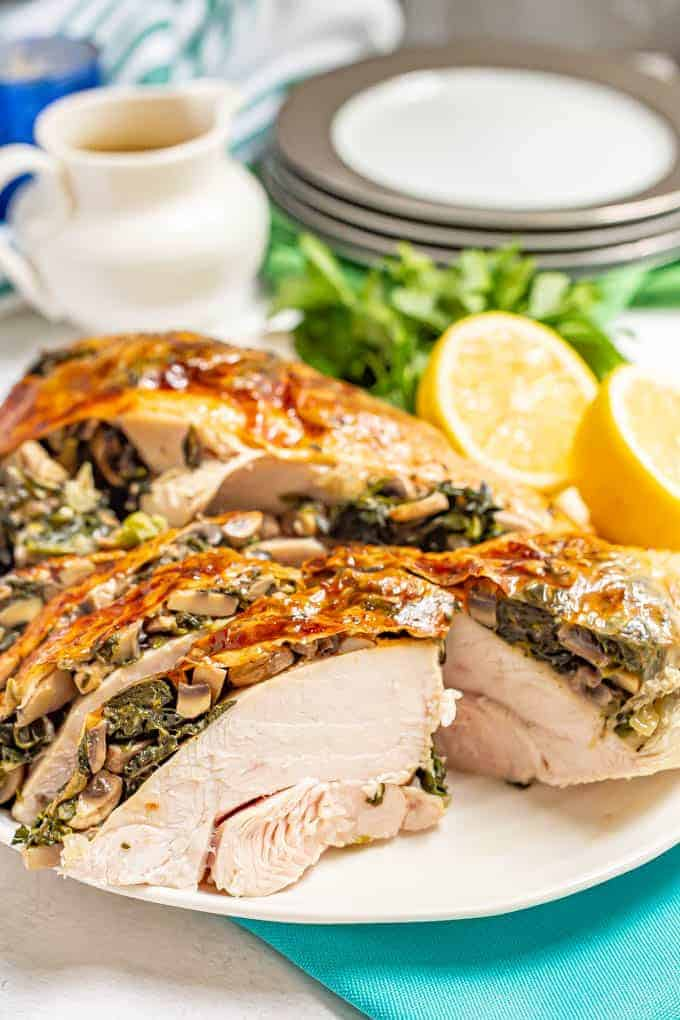 Close up of stuffed spinach and mushroom turkey breast served on a large white platter