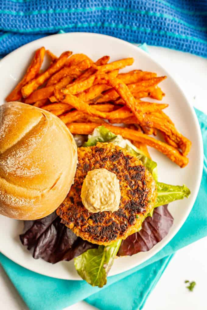 Golden brown chickpea burger served on a bun with lettuce and hummus and a side of sweet potato fries