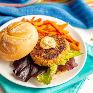 Golden brown chickpea burger served with lettuce and hummus and a side of sweet potato fries