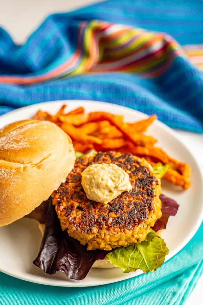 Chickpea burger served on a bun with lettuce and a dollop of hummus