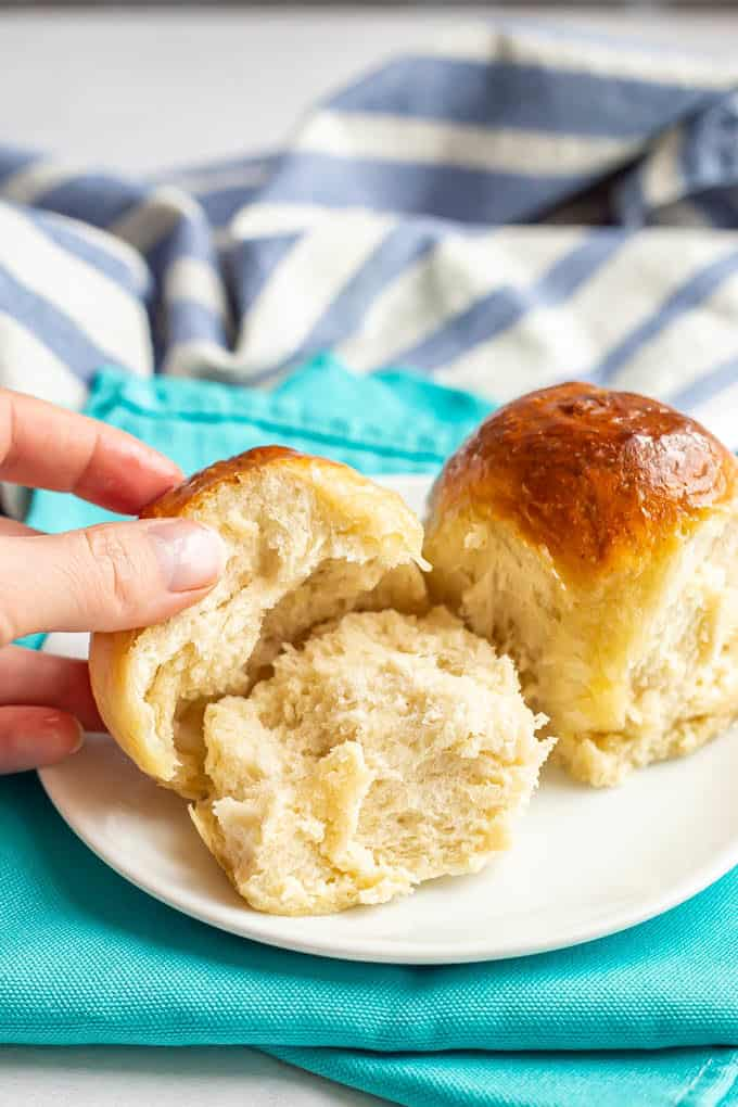 Soft dinner rolls on a white plate with the top half being lifted off of one
