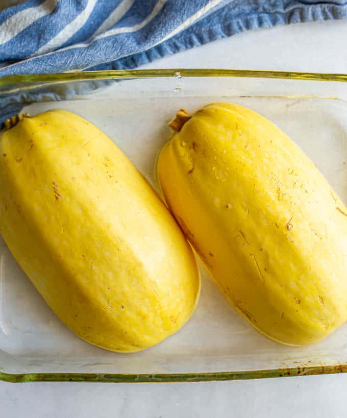 Spaghetti squash halves upside down in a glass pan before being cooked