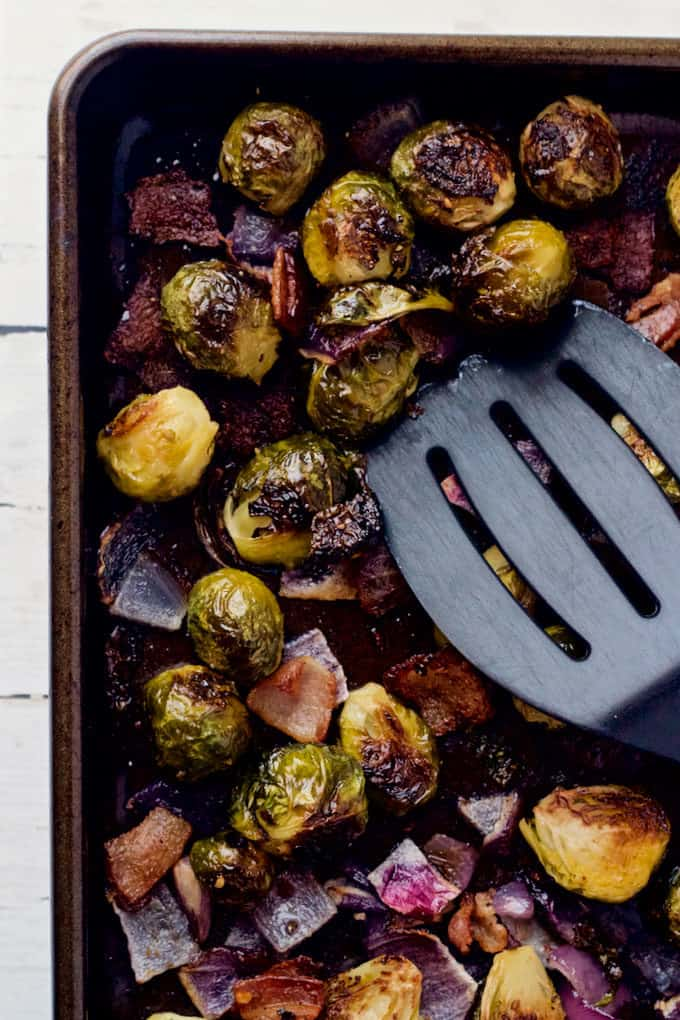 Roasted Brussels sprouts on a sheet pan with a spatula