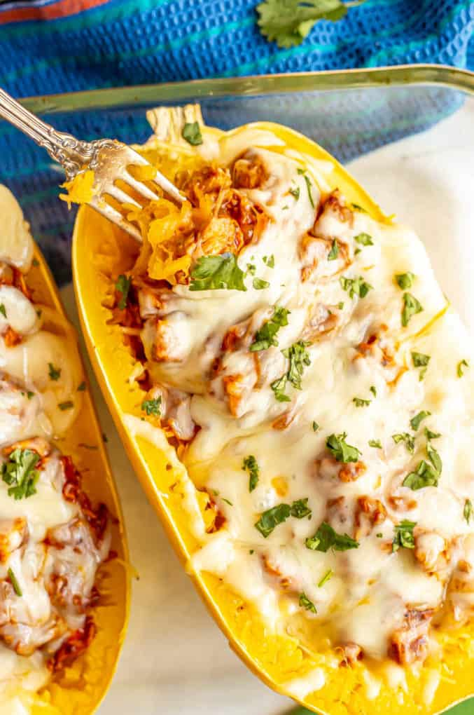 Baked spaghetti squash with chicken enchilada and melted cheese in a casserole dish