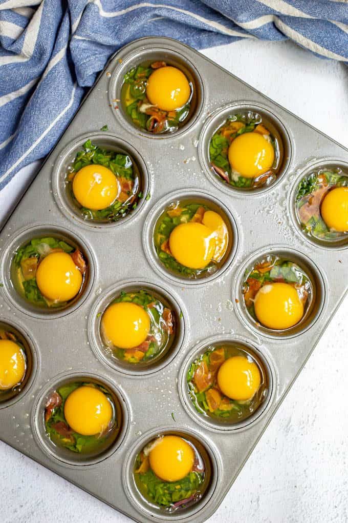 Eggs cracked into a muffin tin before being baked