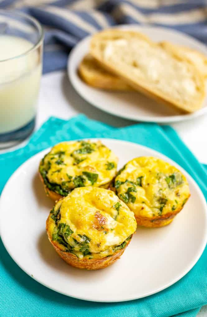 3 egg muffins with spinach and bacon served on a small white plate with toast and milk in the background