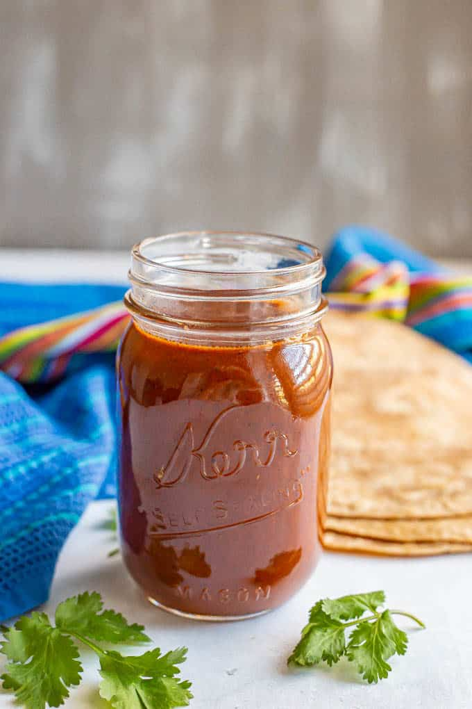 Homemade red enchilada sauce in a glass jar with cilantro sprigs in front