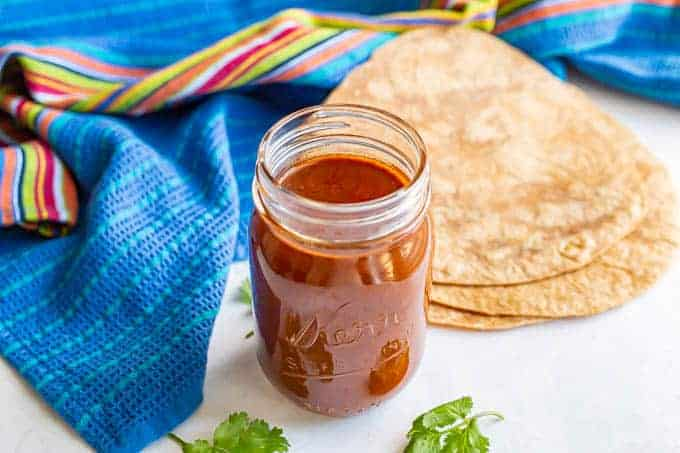A glass jar with homemade enchilada sauce with some stacked tortillas and a colorful blue towel nearby