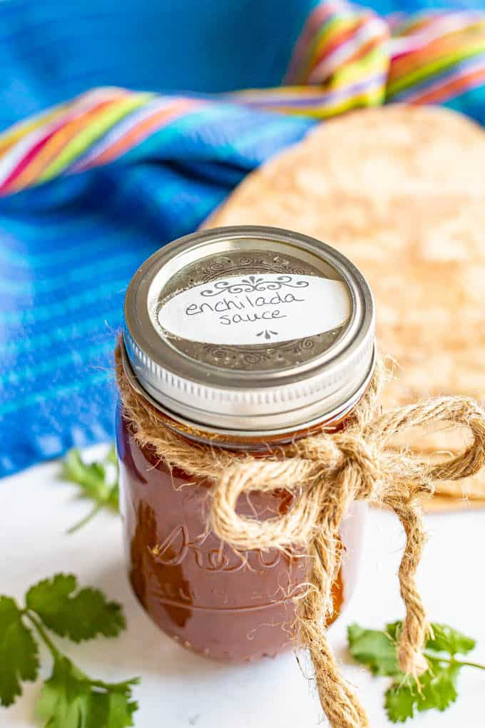 A jar of enchilada sauce with a label on top and a rope tied into a bow around it