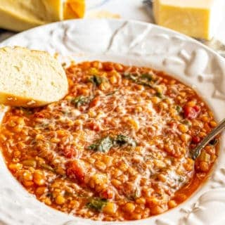 Lentil soup served in a white bowl with Parmesan cheese and fresh bread