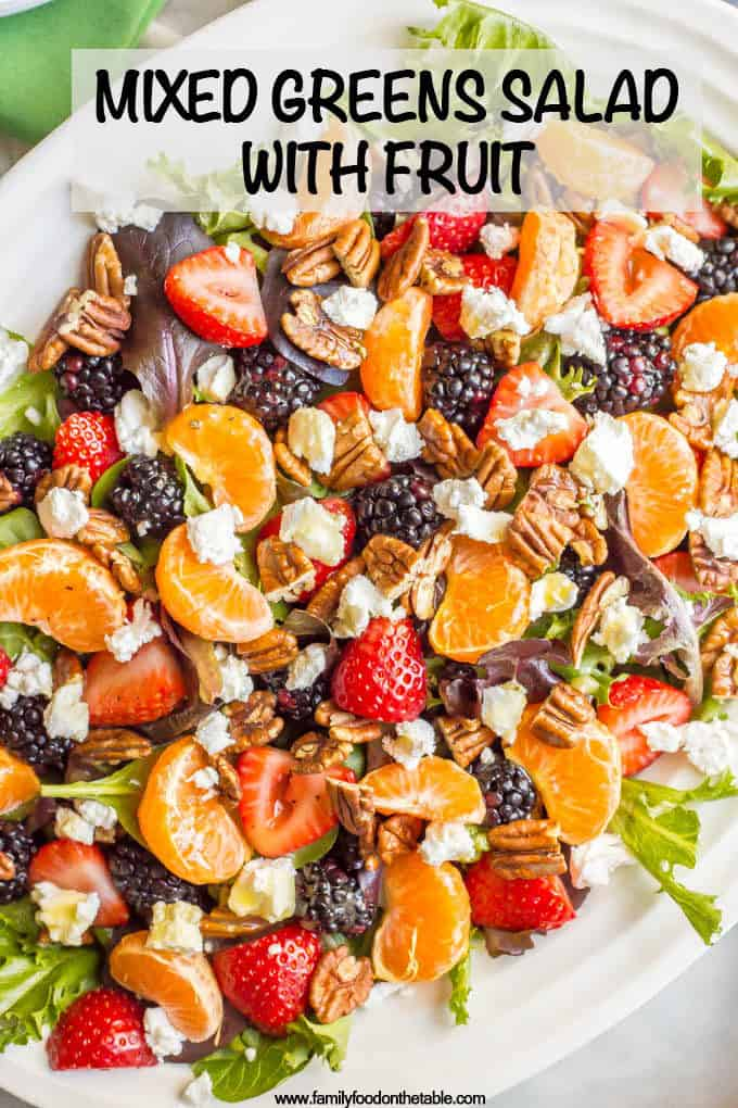 This mixed greens salad with fruit, goat cheese and nuts is perfect for a beautiful side dish or brunch spread! It comes together quickly and is finished with a super easy honey-lime vinaigrette. #brunchsalad #brunch #greensalad #saladlover