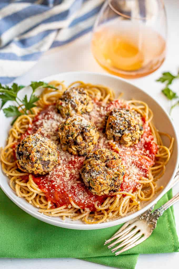 Baked mushroom meatballs served on top of spaghetti and marinara sauce with a glass of rose wine in the background