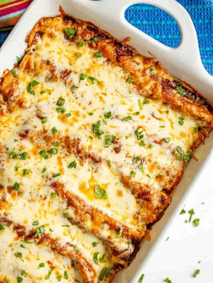 Bubbly cheesy baked sweet potato black bean enchiladas in a white casserole dish