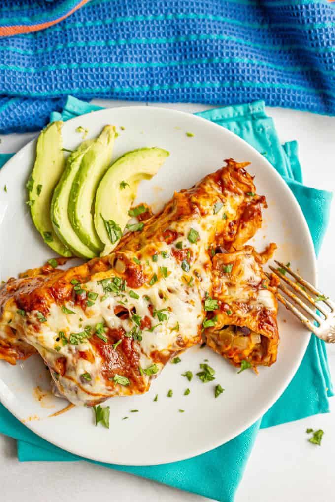 Sweet potato black bean enchiladas served on a plate with cilantro and avocado slices