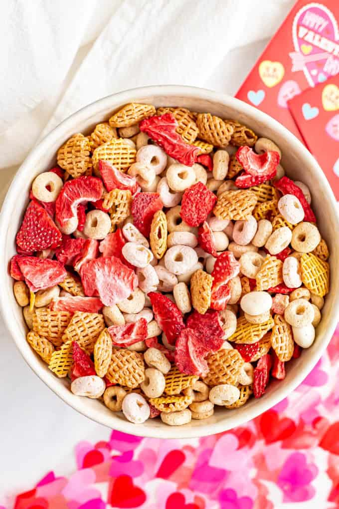 A bowl full of a pink and red colorful Chex mix with cereal and dried strawberries