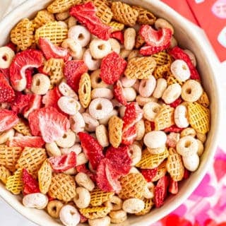 A bowl full of a pink and red colorful Chex mix with cereal, dried strawberries and yogurt covered raisins
