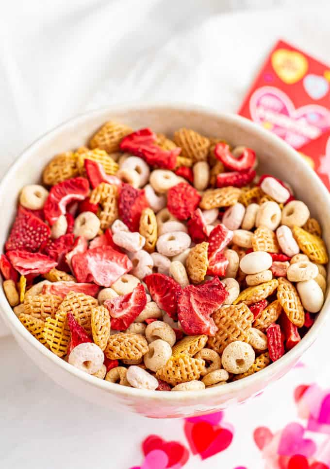 A bowl of healthy Chex mix with cereal, dried strawberries and yogurt covered raisins