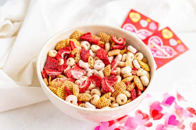 A healthy Valentine's Day snack mix with cereal, yogurt covered raisins and dried strawberries